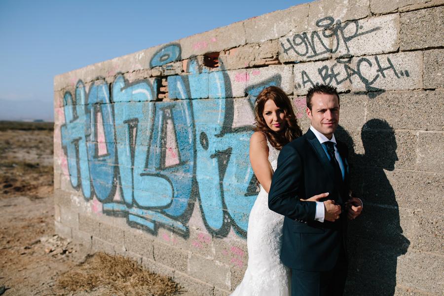 Pareja de novios en cabo de gata junto a un grafitti